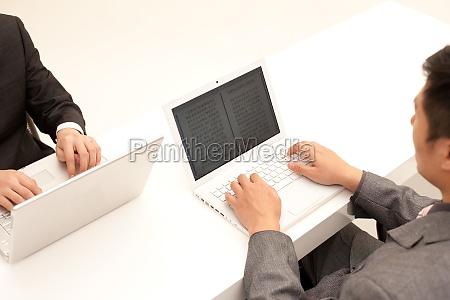 zwei maennliche angestellte mit laptop