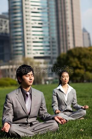 geschaeftsleute die yoga im freien praktizieren