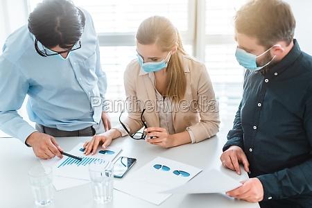 geschaeftsleute die waehrend der besprechung masken