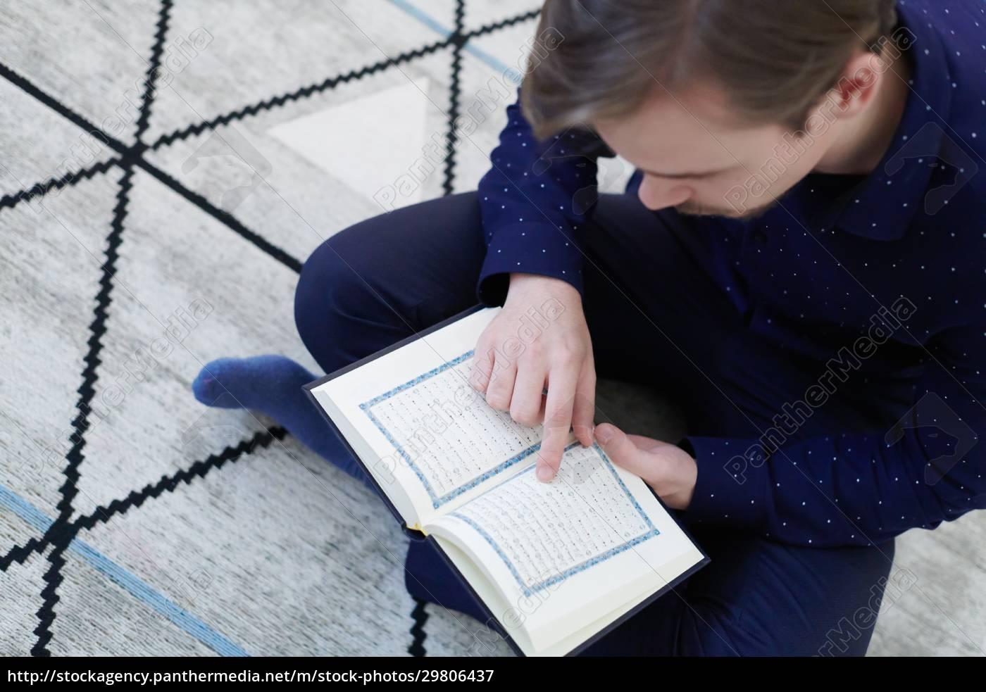 young, muslim, man, reading, quran, at - 29806437