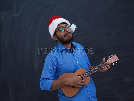 indischer mann traegt santa claus weihnachten