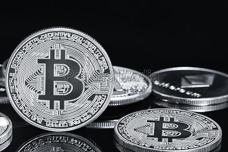 silbermuenzen mit bitcoin symbol auf schwarz