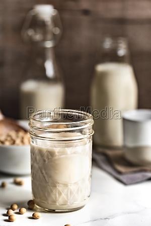 hausgemachte sojamilch in maurerglas und flaschen