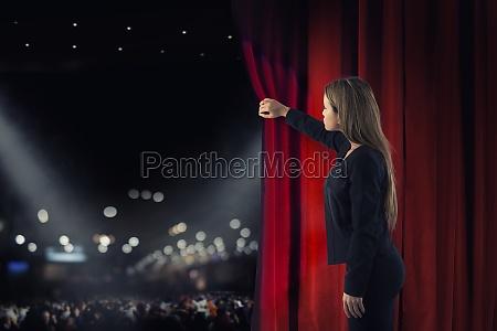 frau oeffnet rote vorhaenge der theaterbuehne