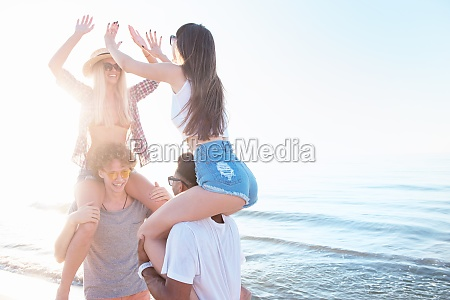 gluecklich laechelnde paare spielen am strand