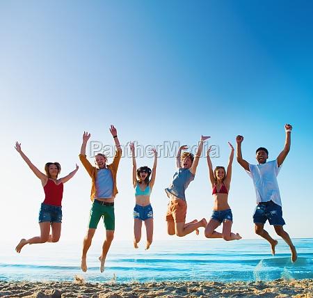 gluecklich laechelnde freunde springen am strand