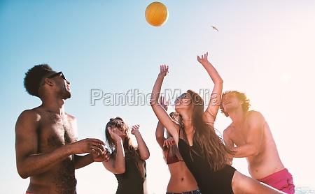 gruppe von freunden spielen bei beachvolleyball