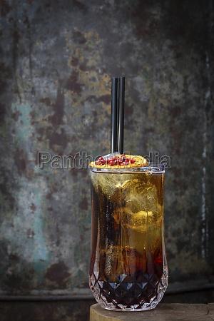 cocktail garniert mit orangenscheiben und beeren