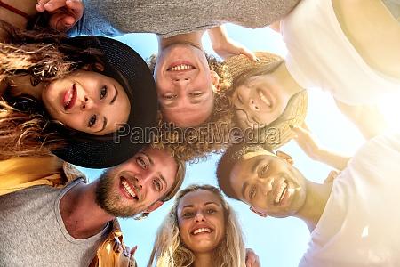 gluecklich laechelnd zusammen freunde am strand