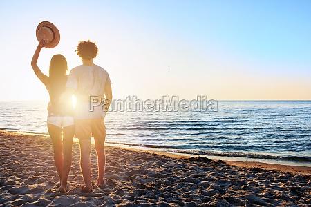 paare bei sonnenaufgang am strand beobachten