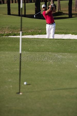 golfer schlaegt einen sandbunkerschuss