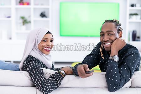 afrikanisches paar sitzt auf sofa und