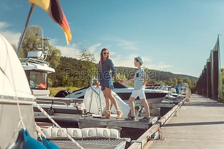 mutter und sohn betreten ein motorboot