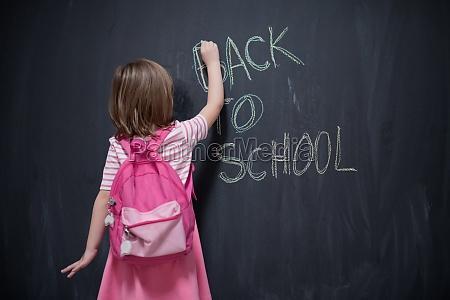 schule maedchen kind mit rucksack schreiben