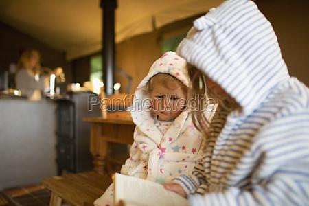 suesse schwestern in kapuzenbademaenteln lesen buch