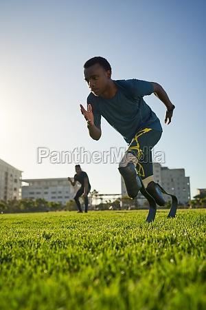 fokussiertes maennliches amputierter sprintertraining auf sonnigem