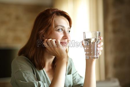 zufriedene frau die wasserglas zu hause