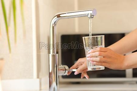 frauenhaende fuellen ein glas leitungswasser